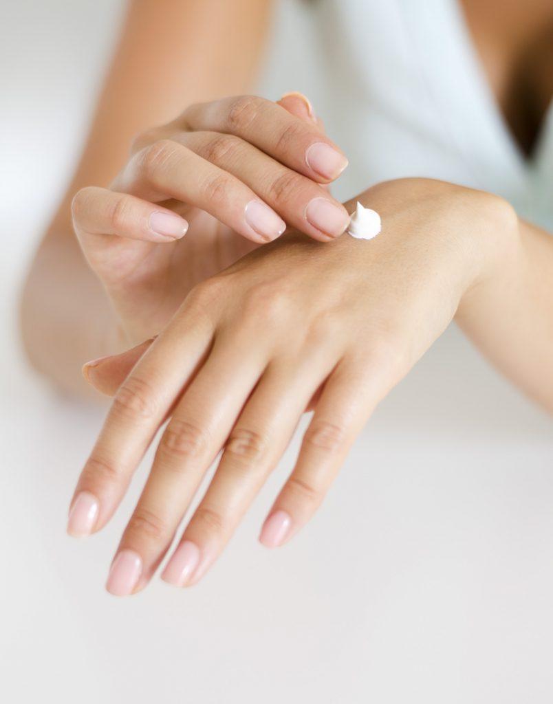 woman applying sunscreen to hand