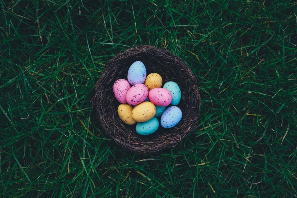 colored Easter eggs in a basket on grass