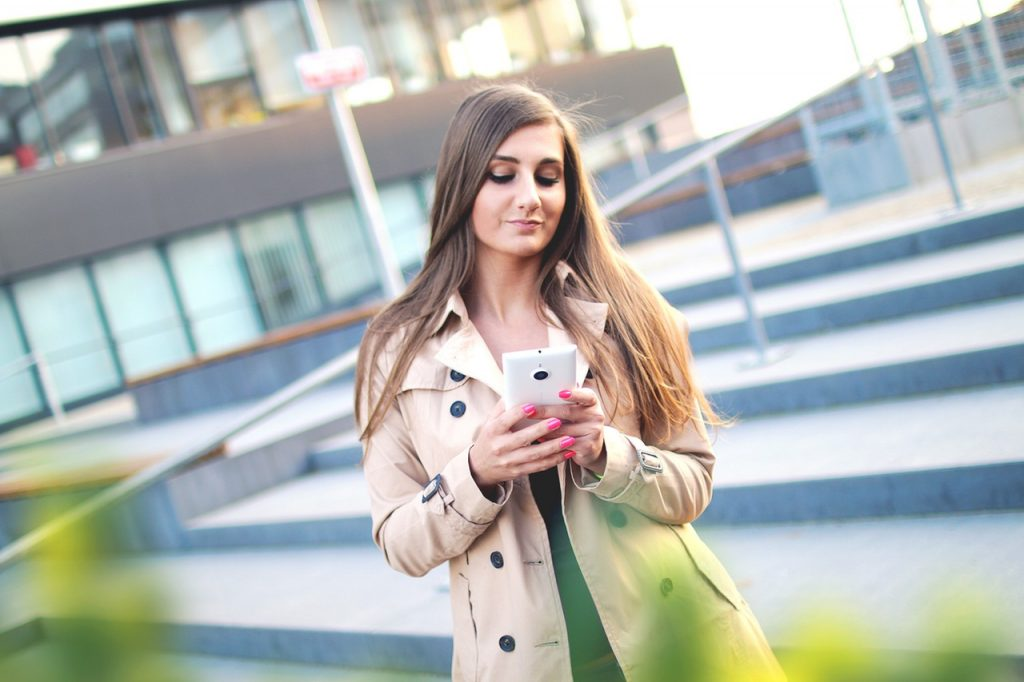 woman looking at cell phone outside